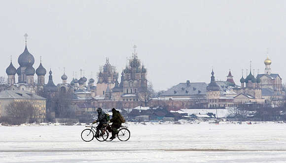 Men ride bicycles on ice of a lake in front of the cathedrals of the Kremlin in Rostov Veliky, about 200km from Moscow.