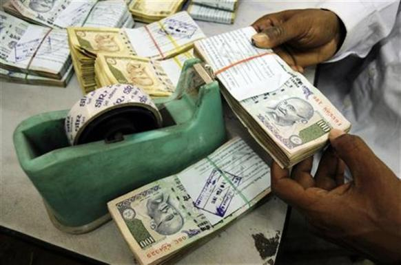 An employee arranges currency notes at a cash counter inside a bank in Agartala.