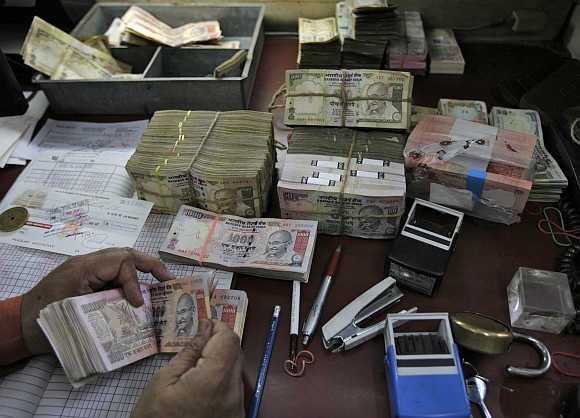 An employee counts rupeee notes at a cash counter inside a bank in New Delhi.