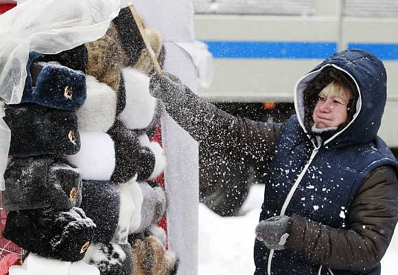 A shop assistant removes snow from Russian traditional hats, also known as Ushanka hats, near Red Square during heavy snowfall in central Moscow.