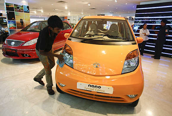 A showroom attendant cleans a Tata Nano at their flagship outlet in Mumbai.