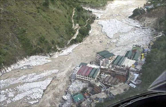 Flood waters flow next to a residential complex after heavy rains in Uttarakhand.