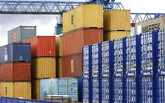 Shipping containers stand in a transport yard.
