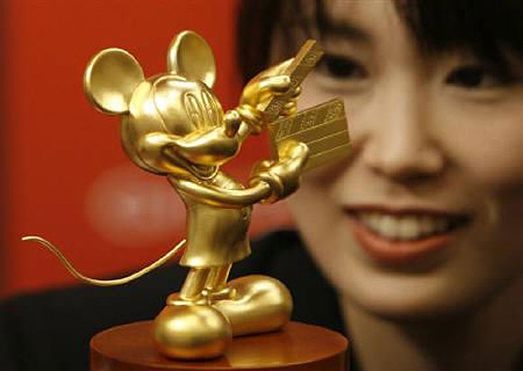 Ayako Kikuchi, an employee of jewellery maker Ginza Tanaka, poses with a statue of Mickey Mouse in Tokyo.