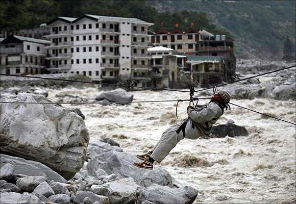 A man is pulled across to safety on a rope, as damaged buildings and the Alaknanda river are seen in the background, during a rescue operation in Govindghat in the Himalayan state of Uttarakhand.