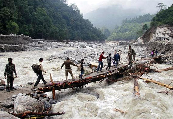 Indian army personnel help stranded people cross a flooded river after heavy rains in the Himalayan state of Uttarakhand.