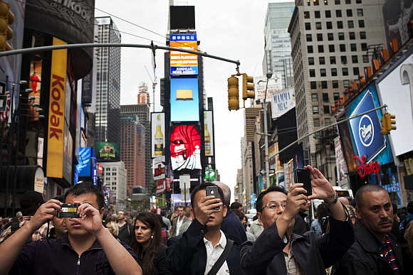 People take photos in Times Square in New York City.