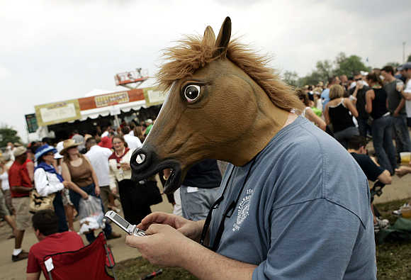 A spectator, wearing a mask in the shape of a horse's head, uses his mobile phone before the running of the Kentucky Derby at Churchill Downs in Louisville, Kentucky, United States.