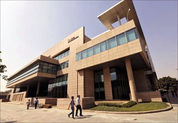 Employees walk inside Tech Mahindra office premises in Noida on the outskirts of New Delhi.