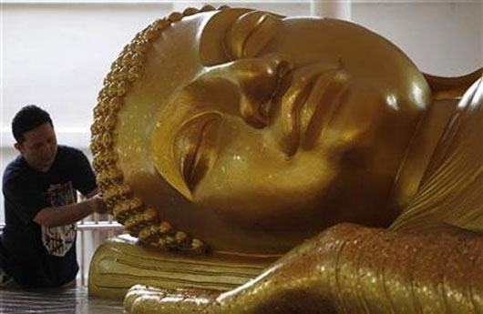 A man gild gold on a Buddha statue in a temple in Bangkok.