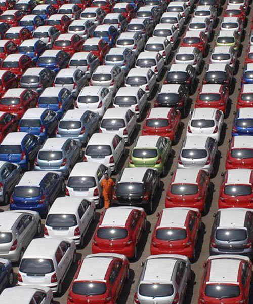 Workers walk beside cars ready for shipment at a harbour in Chennai.