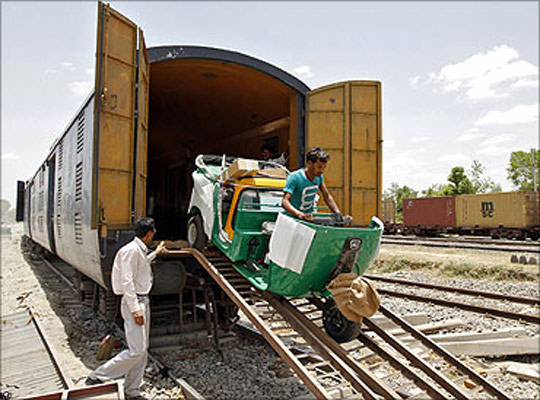 A new auto rickshaw is unloaded from a goods train at a storage facility at Sanand.