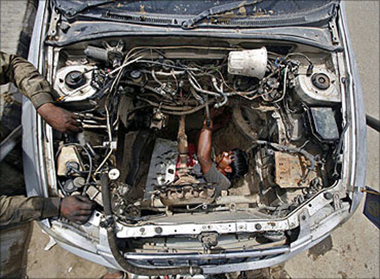 A mechanic dismantles the engine of a car at a workshop in Noida.