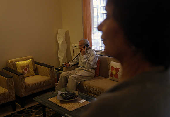 Aruna Gokhale, 81, watches as her husband Vidyadhar Gokhale, 84, speaks on the phone in their flat at the Athashri retirement village in Baner, on the outskirts Pune.