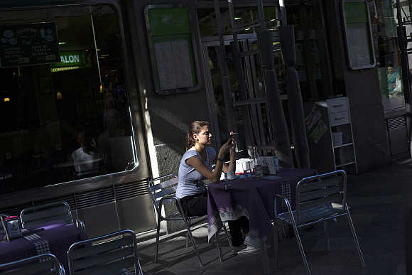 A woman checks her mobile phone at a shopping district in Madrid, Spain.