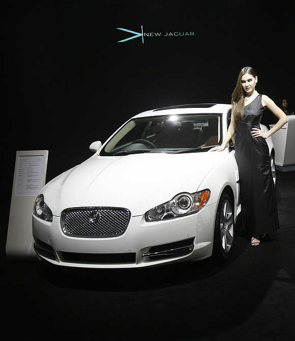 A model poses with a Jaguar XF at India's Auto Expo in New Delhi.