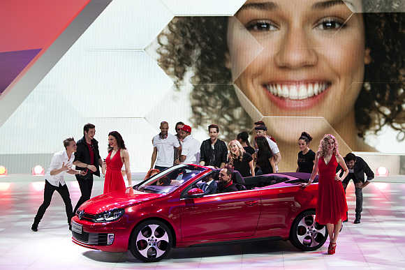Models surround Volkswagen Golf GTI Cabriolet car in Geneva, Switzerland.