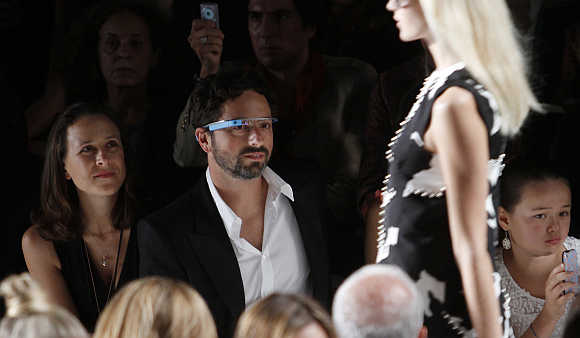 Google's co-founder Sergey Brin, wearing Google Glasses, and a guest watch a fashion show New York.