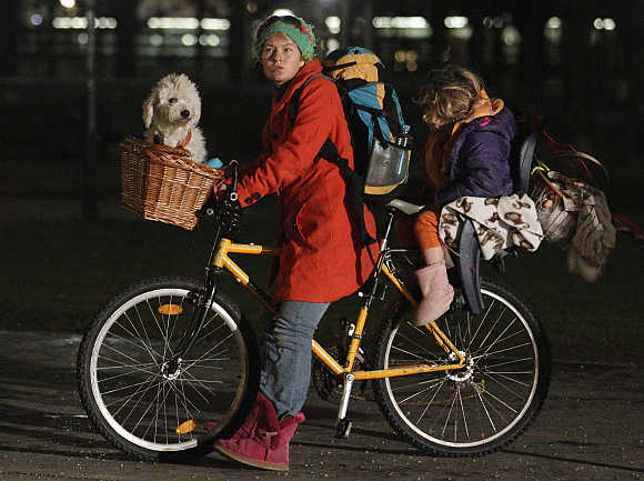 A woman on a bicycle with a dog and a child in Vienna, Austria.