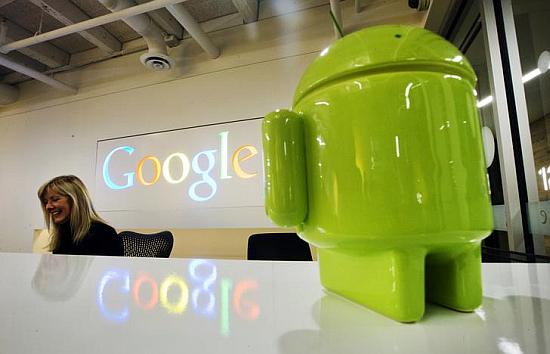 A Google Android figurine sits on the welcome desk as employee Tracy McNeilly smiles at the new Google office in Toronto.