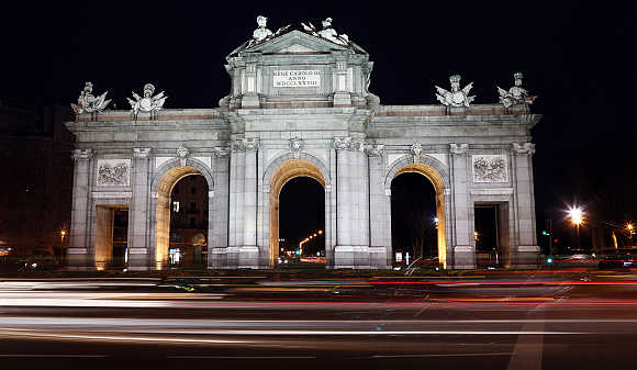 Traffic passes in front of the Alcala Gate, one of Madrid's famous landmarks in Spain.