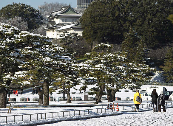 People walk near the Imperial Palace covered with snow in Tokyo, Japan.
