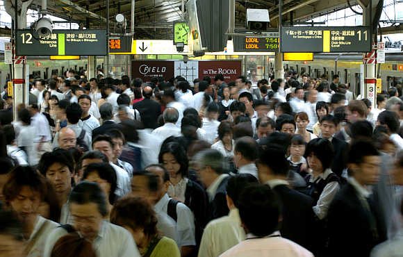 Commuters make their way to various destinations during rush hour at a train station in Tokyo, Japan.