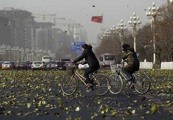 Cyclists cross Chang'an Avenue amid strong winds in central Beijing, China.