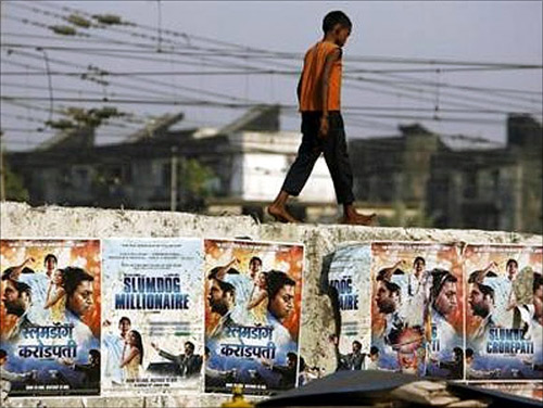 A boy living on the street walks on a wall displaying publicity posters of Golden Globe award-winning film.