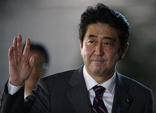 Japan's Prime Minister Shinzo Abe waves as he arrives at his official residence in Tokyo.