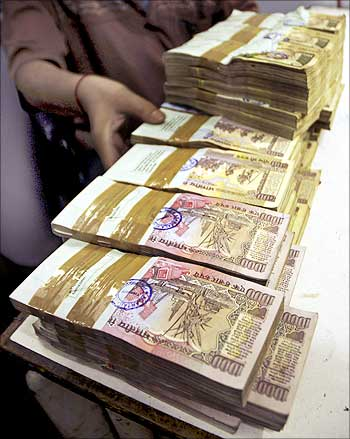 A teller arranges stacks of rupee notes in a bank.