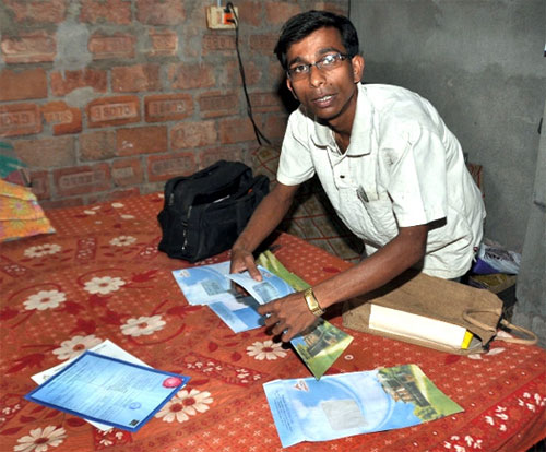 Siddhartha Das, a Saradha agent, goes through his investment papers at his make-shift home.
