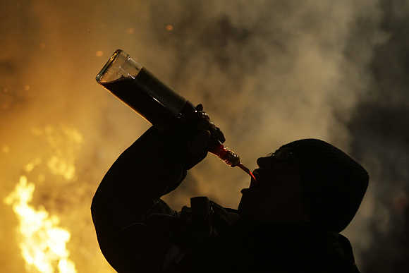 A man downs alcohol during the annual Saint Anthony purification ceremony in the village of San Bartolome de los Pinares near Avila in Spain.