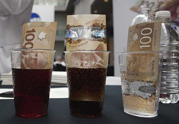 Canadian 100 dollar bills made of polymer are placed in glasses of juice, cola and water in Toronto. Plastic notes, nearly impervious to liquids, stains, tearing or wear-and-tear, were pioneered by the Reserve Bank of Australia in 1988.