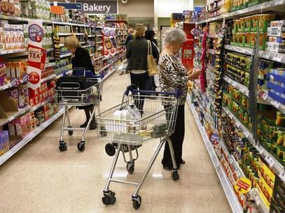 Customers shop for groceries in a supermarket.
