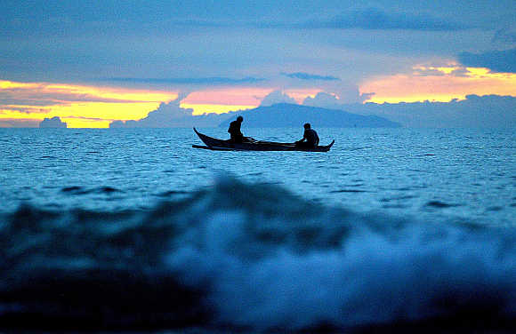 Fishermen prepare their nets as they sail during sunset in Puerto Galera province of Oriental Mindoro, some 120km southwest of Manila, the Philippines.