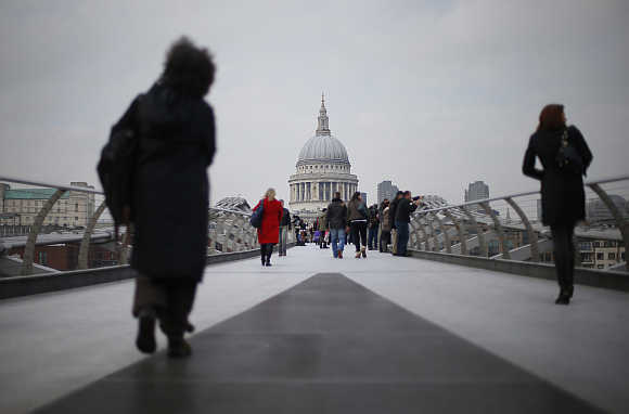 Two women walk along the Millennium footbridge crossing the River Thames towards St Paul's Cathedral in central London, United Kingdom.