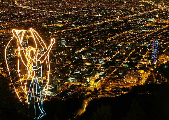 An illuminated Christmas decoration of an angel overlooks Bogota city in Colombia.