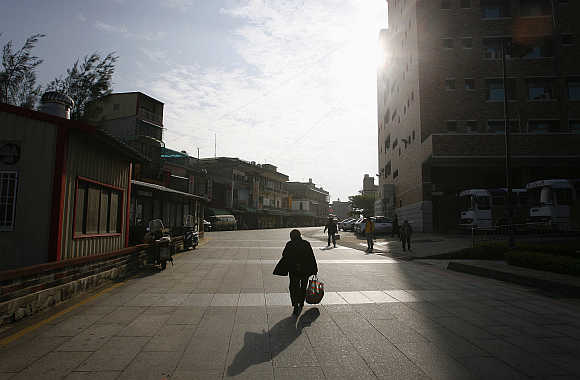 A woman walks along a street at a market in Kinmen County. Kinmen, near Xiamen, China, is a small archipelago of several islands administered by Taiwan.