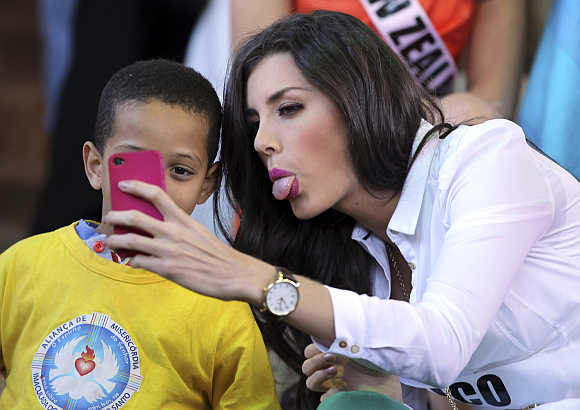 Miss Mexico 2011 Karin Ontiveros jokes with a boy as she takes a photograph in Sao Paulo, Brazil.
