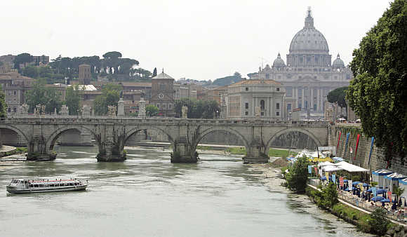 A tourist boat glides past sunbathers lying on a small artificial beach, right, on the banks of the Tiber River in Rome, as the Vatican's St Peter's Basilica is seen on the top.