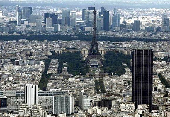 The Eiffel tower, la Defence business district (background) and the Montparnasse tower (R) are seen in an aerial view in Paris.