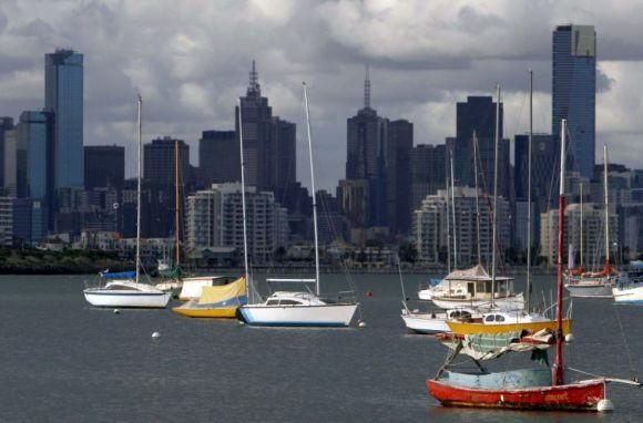 Sailboats dock in front of the Melbourne skyline.