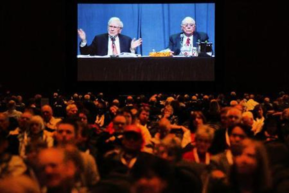 Berkshire Hathaway shareholders listen as Chairman Warren Buffett (L) and Vice Chairman Charlie Munger, seen on a video screen, answer questions at the company's annual meeting in Omaha.