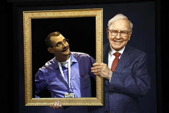 Richard Harmon (L), a Berkshire Hathaway shareholder, poses in an opening in a wall behind a picture frame held by a photograph of Berkshire Chairman Warren Buffet, at the company's annual meeting in Omaha.