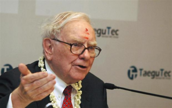 Billionaire Warren Buffett, wearing a traditional tikka or a red mark on the forehead, speaks during a news conference in Bangalore.