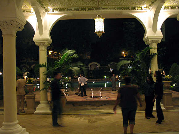 Guests walk by the poolside area of Taj Mahal hotel in Mumbai.