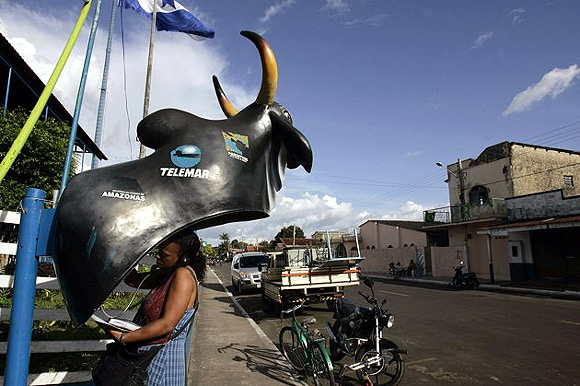 A tourist talks at a public phone booth fashioned to look like an ox, during the Parintins jungle carnival deep in the heart of the Amazon forest.