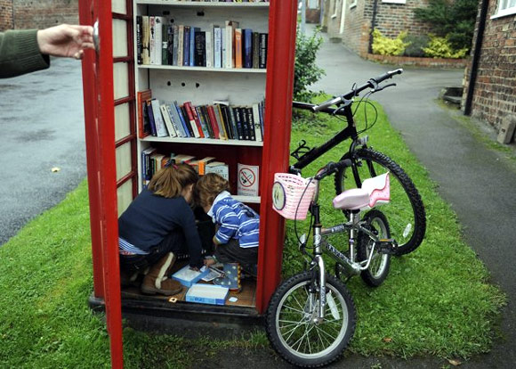 Duncan Berry holds the door open as his children Jemima (L) and Hugo choose books from the village phone box in Marton cum Grafton, northern England.