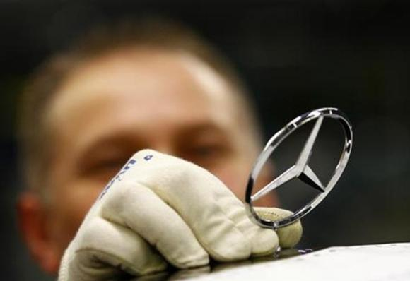 An employee of German car manufacturer Mercedes Benz installs the characteristic Mercedes star on the bonnet of a Mercedes S-class.
